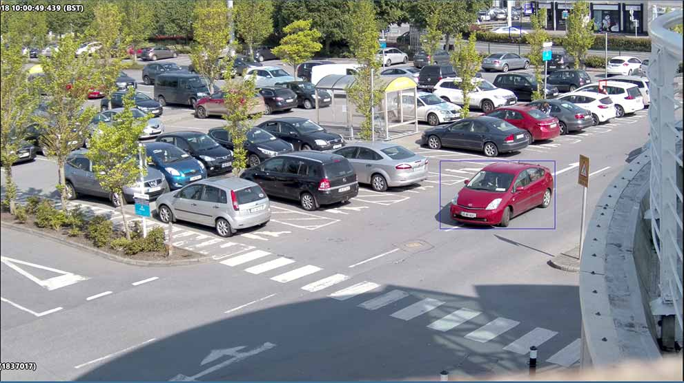 view of shopping centre carpark with red car highlighted as seen from avigilon cctv camera