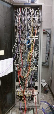 comms cabinet 'before' image - coloured wires handing out of tall narrow cabinet